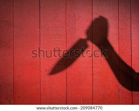 Male Hand Shadow with Kitchen Knife, on wood wall - stock photo