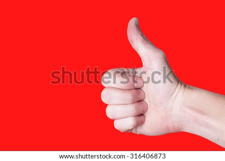 Male hand showing thumbs up sign sign isolated on red background