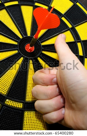 Male hand showing thumbs up with bulls eye on dart game board - stock photo