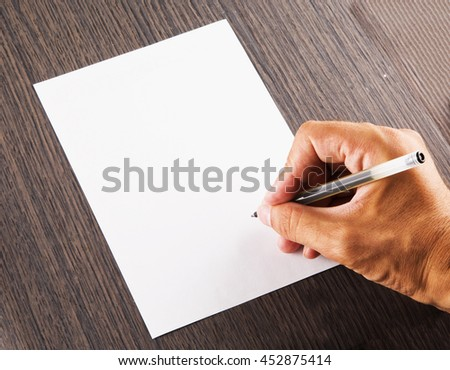 Male hand signing a white sheet of paper, horizontal image - stock photo