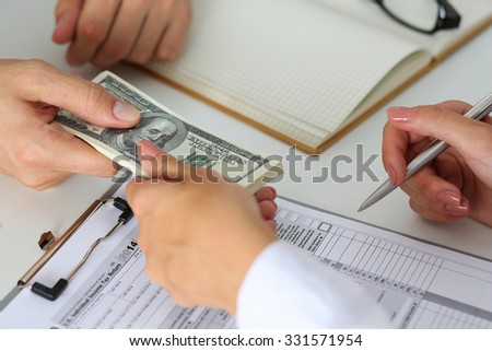 Male hand taking or giving bunch of hundred dollars bank notes to woman closeup. Female hand accepting cash payment from man. IRS, bribe and bribery, collusion, crime, revenue report concept - stock photo