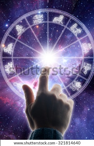 male hand touching an astrology chart - background image provided by NASA - stock photo