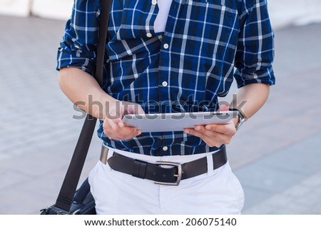 Male hand touching digital tablet pc. Outside photo - stock photo