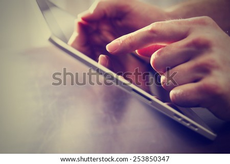 male hand touching tablet with finger tip while holding on a table with a retro instagram filter (shallow depth of field)