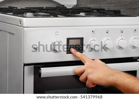 Male hand turning on white kitchen gas stove on gray background