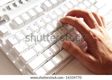 male hand typing on a computer keyboard with high contrast effect