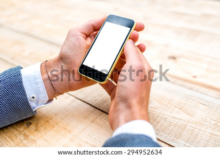 Male hand using a phone with isolated screen on wooden table  - stock photo