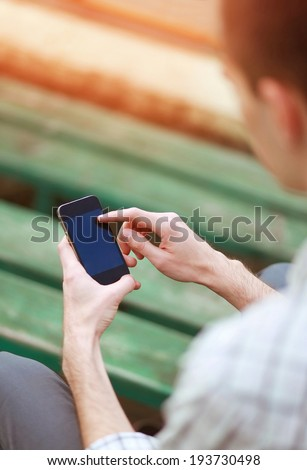 Male hand using a smart phone. Modern vintage hipster photo - stock photo
