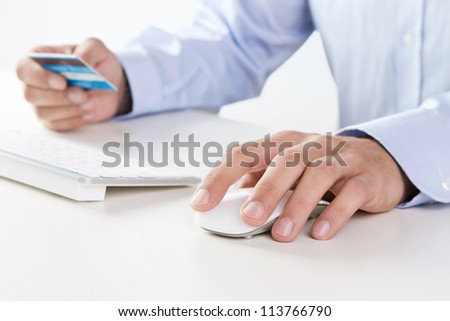 Male hand using computer and credit card for online payment - stock photo