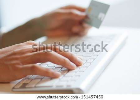 Male hand using computer keyboard and holding credit card for online payment - stock photo