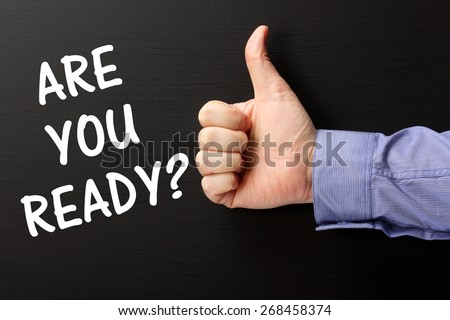 Male hand wearing a business shirt giving the thumbs up gesture to the phrase Are You Ready in white text on a blackboard