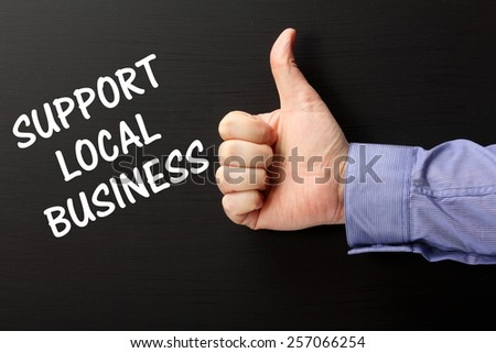 Male hand wearing a business shirt giving the Thumbs Up gesture to the phrase Support Local Business written on a blackboard