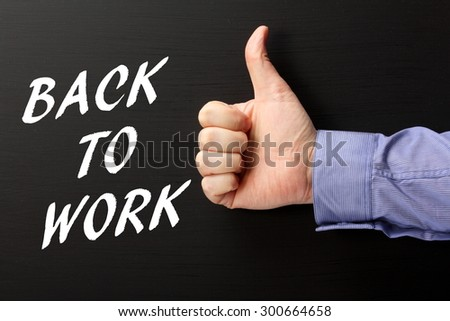 Male hand wearing a business shirt giving the thumbs up sign to the phrase Back to Work in white text on a blackboard