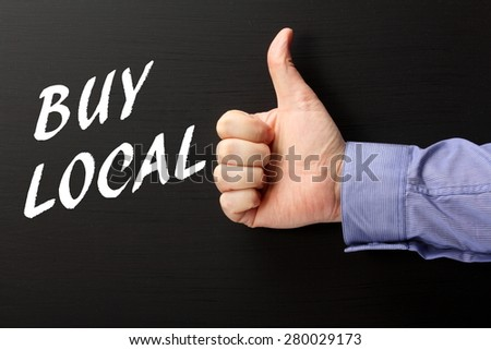 Male hand wearing a business shirt giving the thumbs up sign to the phrase Buy Local in white text on a blackboard