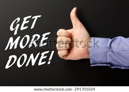 Male hand wearing a business shirt giving the thumbs up sign to the phrase Get More Done in white text on a blackboard