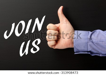 Male hand wearing a business shirt giving the thumbs up sign to the phrase Join Us in white text on a blackboard