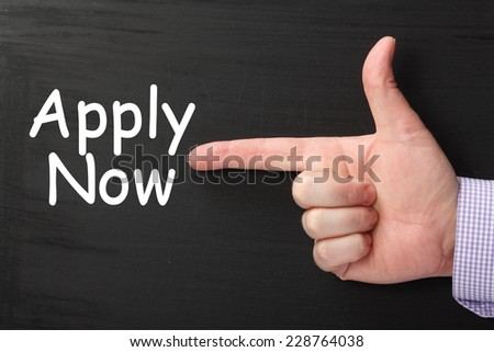Male hand wearing a business shirt pointing a finger at the phrase Apply Now on a blackboard - stock photo
