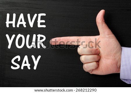 Male hand wearing a business shirt pointing at the phrase Have Your Say in white text on a blackboard - stock photo