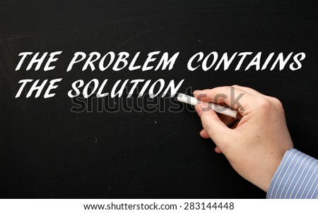 Male hand wearing a business shirt writing the phrase The Problem Contains The Solution in white text on a blackboard - stock photo