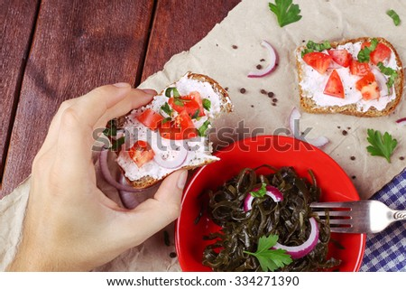 Male hand with a fork and a sandwich. Lunch, food, snack. Laminaria and bruschetta. Sandwiches with cheese paste, herbs and tomatoes. Marine cabbage salad. Food on the table. Healthy food. Appetite.  - stock photo