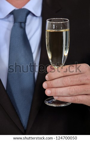 Male hand with a glass of champagne - stock photo