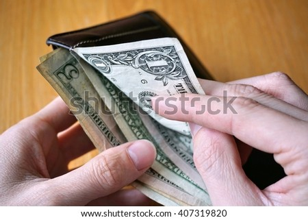 Male hand with a leather wallet, right hand is pulling American Dollars (USD, US Dollars)
