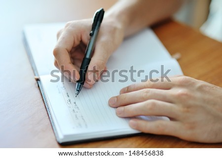 male hand with a pen writing on a white paper notebook