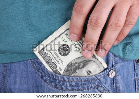 Male hand with cash. US dollars in the man's hand. Banknotes in the pocket. Bribe, cash, financing, start up. To buy, paying cash. A lot of money in his hand. Men's hand and dollars. - stock photo