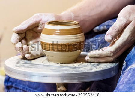 Male hand with clay pot with pattern on a pottery wheel - stock photo