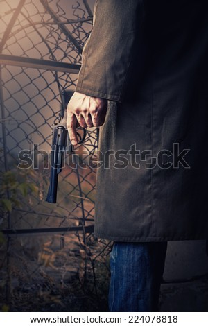Male Hand with gun (revolver) outdoor.   - stock photo