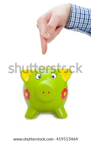 Male hand with index finger indicating on green piggy bank