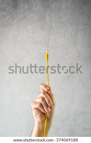 Male hand with LAN cable connecting to network, local area connection concept. - stock photo