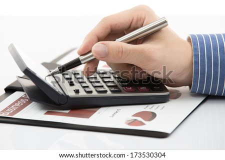 Male hand with pen analyzing financial data. Accounting - stock photo