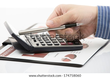Male hand with pen analyzing financial data. Accounting
