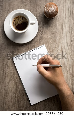 Male hand with pen on empty paper, writing on coffee break