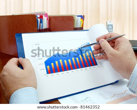 Male hand with pen on the investment chart. - stock photo