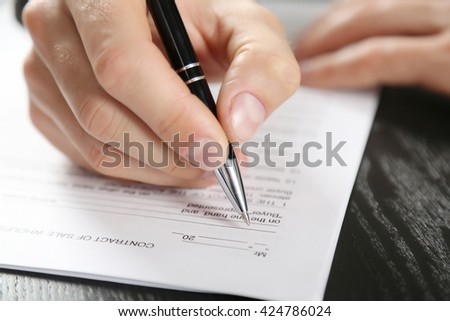 Male hand with pen signing document at the desk closeup - stock photo