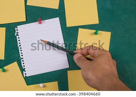 Male hand with pen writing on notebook?Blank Yellow paper, posted ,post-it ,note ,Sticky Note ? - stock photo