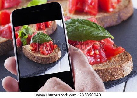 Male hand with smartphone taking a photo of food - stock photo