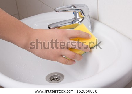 Male hand with sponge cleaning white sink - stock photo