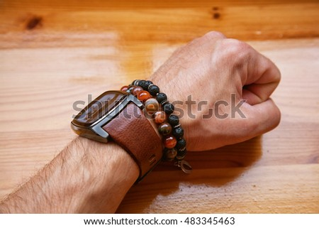 male hand with the watch and bracelets