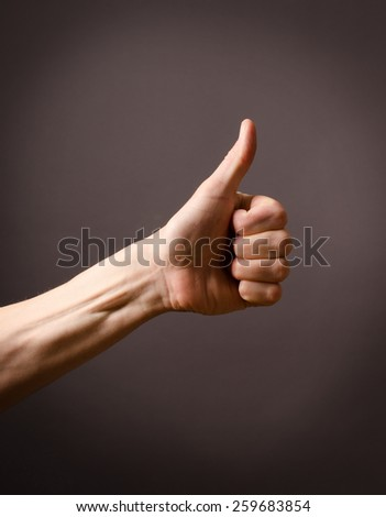 Male hand with thumb up on a dark background - stock photo