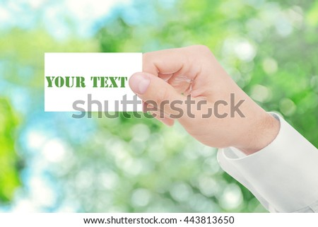 Male hand with white blank card on abstract nature blurred background - stock photo
