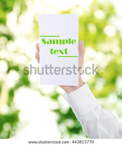 Male hand with white paper on blurred natural background - stock photo