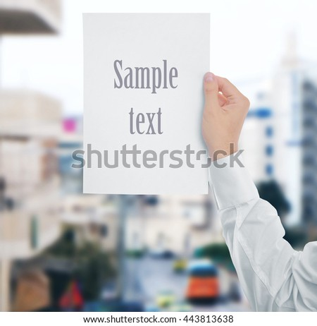 Male hand with white paper on blurred street background - stock photo