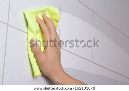 male hand with yellow rag cleaning the bathroom tiles - stock photo