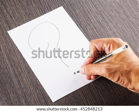 Male hand writing a question mark, horizontal image