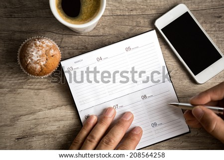 male hand writing at planning notebook on wooden desk - stock photo