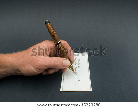 male hand writing check to savings for more dollars needed - stock photo