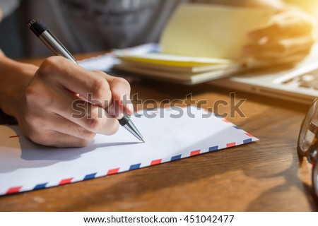 male hand writing down on letter paper on the wood desk.